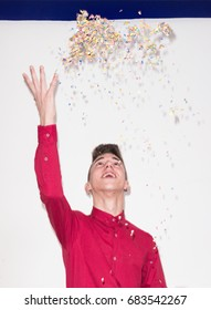 throwing confetti, white background studio, one Caucasian teenager portrait, looking up above, upper body shot, red shirt