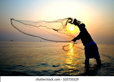 Photo of throwing fishing net during sunrise, Thailand