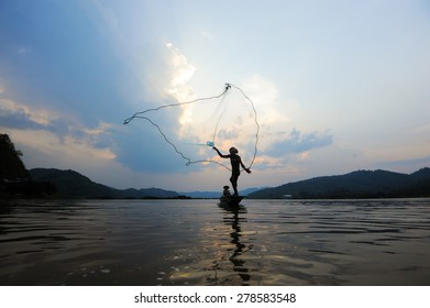 throwing fishing net during sunset on boat , thai, silhouette