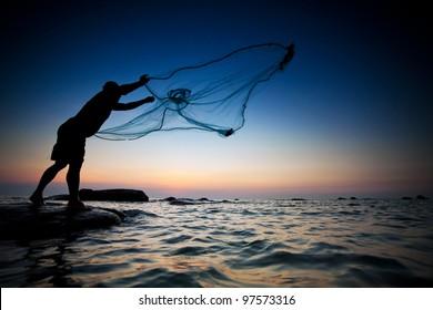 throwing fishing net during sunset , thai