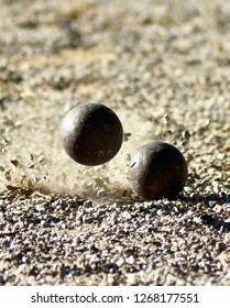 Throwing iron boules and bumping into the ground, graveling and impacting other balls until the gravel splashes, this is a training course in sports.