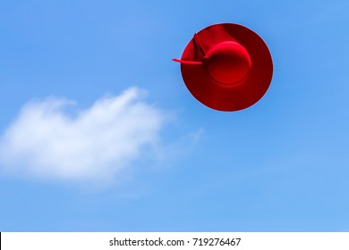 Throwing velvet red hat up to the air, on the blue sky background, feeling happy, refresh, relax, and free your mind. Travel and leisure concept.