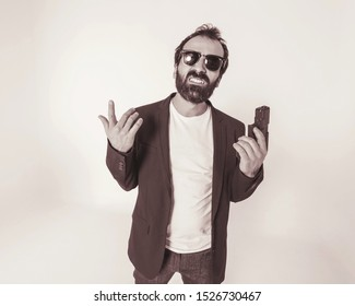 A thug man with a beard and glasses holds a gun in hand and shows teeth