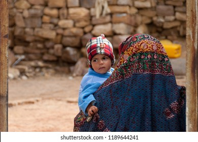 Thula, Yemen - May 5, 2007: A woman in traditional colorful clothes walks with her little son in her arms. Although infant mortality is high, children in Yemen are socially valued.