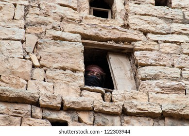 THULA, YEMEN - MAY 5: An unidentified woman looks through her window on May 5, 2007 in Thula, Yemen. Modern day women of Yemen do not hold many economic, social or cultural rights.