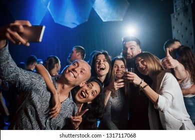 Thumb and alcohol up. Friends taking selfie in beautiful nightclub. With drinks in the hands.