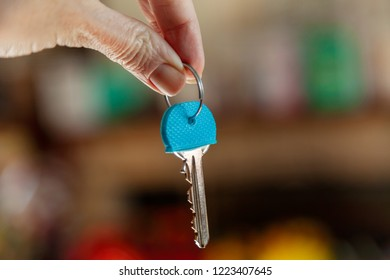 Thumb and finger holding a house door key, with a bokeh background