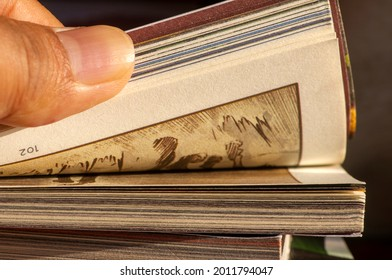 A thumb flipping pages of a comic book in shallow focus