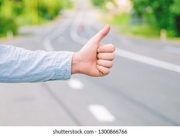 Thumb up gesture try stop car road background. Hand gesture hitchhiking. Make sure you know right gestures to stop car. Thumb up sign not work in many parts of world. Autostop travel. Pick me up.