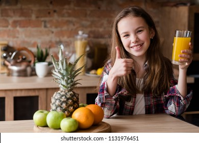 thumb up for healthy eating. little smiling girl holding a glass of fresh organic orange juice. wholesome snack of fruit and beverage.