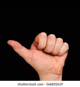 The thumb of the left hand. Men's hand showing one finger on a black background.