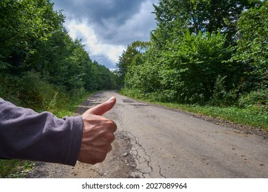 Thumb up on the background of the road. Hitchhiking in the countryside.