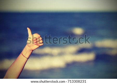 Thumb up to say ok and the background of the sea with vintage effect
