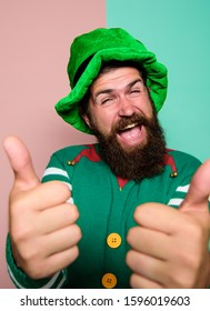 thumb up for success. Winter carnival. irish pub party. st patricks day. happy bearded hipster in green hat. christmas elf. happy celebration. cheerful man with beard have fun. ireland beer tradition.