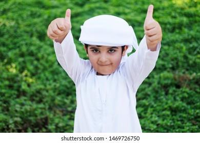 Thumbs up approve gesture by young Emirati Arab boy wearing kandura