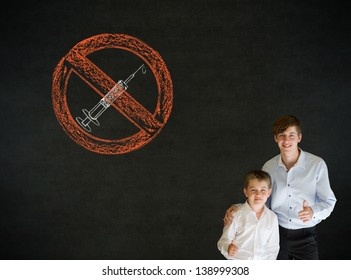 Thumbs up boy dressed up as business man with teacher man and no drugs needle sign on blackboard background