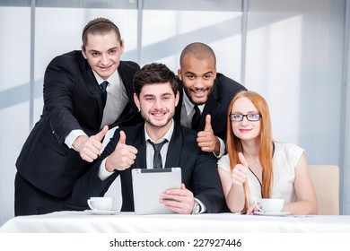 Thumbs up business. Four smiling successful businesspeople sitting at table in office while discussing their business doing. Young people show a thumbs up