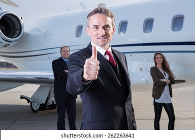 thumbs up business team in front of corporate private jet
