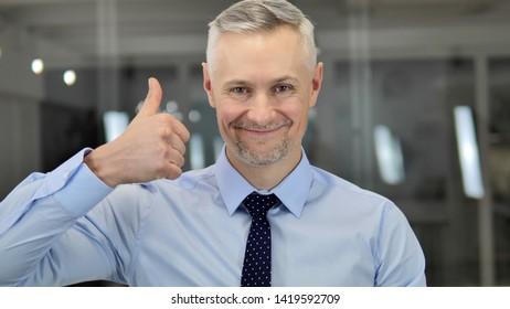 Thumbs Up by Grey Hair Businessman Looking at Camera