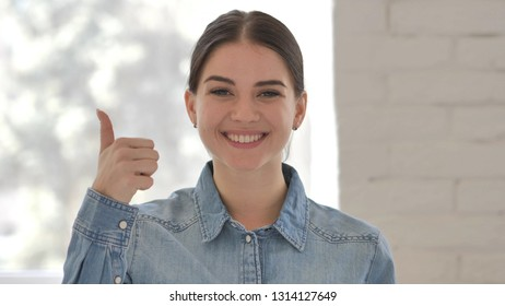 Thumbs Up by Young Girl at Work,  Looking at Camera