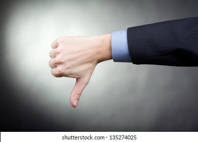 Thumbs down hand sign showing by man