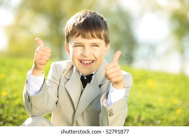 Thumbs up from enthusiastic young boy  in elegant business suit  in nature on a sunny day