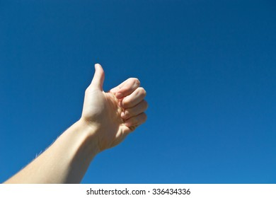 Thumbs up sign in the blue sky. Caucasian