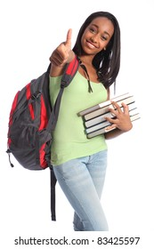 Thumbs up for successful education from pretty young African American teenager student girl with big beautiful smile wearing red backpack and holding school books.