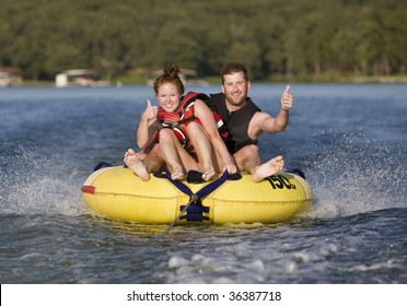 Thumbs up while tubing on a lake