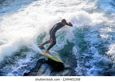 Thun, Switzerland - OCTOBER 14, 2018: Man surfer rides to practice the surfboard on the river wave during sunset with lots of splashes.