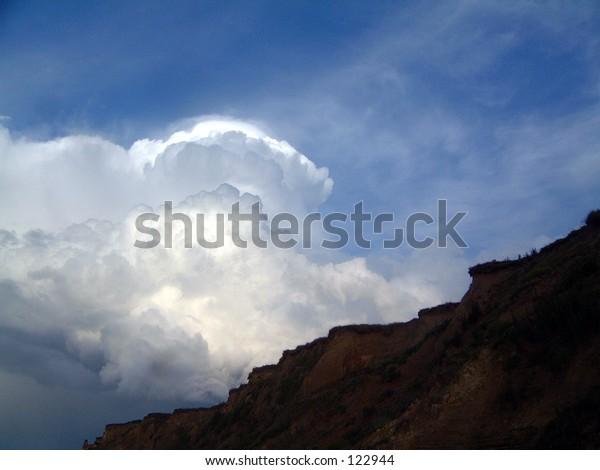 Thunder head beach shore sea sun shadow light golden sunset clouds grass flowers cliff top