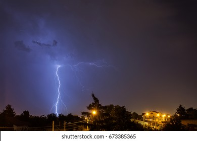 Thunder storm over houses in country side in the middle of the night with beautiful lightning in background