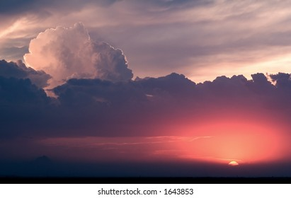 A thundershower builds and kicks up dust as the sun sets