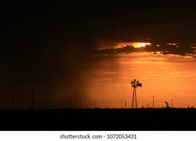 Thundershowers, windmill, and pump jack in the Permian Basin