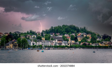 Thunderstorm coming over a city on the lake, city view and boats in the lake waiting for the coming storm