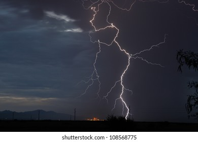 Thunderstorm and dark blue sky with lightning over power plant in Arizona, USA, during summer monsoon/Cloud to Ground Lightning Strike at Twilight during Thunderstorm/Lightning in summer thunderstorm