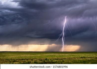 Thunderstorm lightning bolt strike with storm clouds