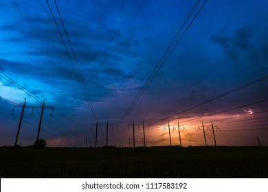 Thunderstorm, lightning and high voltage power lines. Power lines and five electricity pylons on a background of lightning. Beautiful dramatic sky at dusk. Electricity theme.