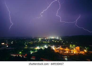 Thunderstorm and lightning over an industrial zone near a small town at night. Ukraine. Lightning and beautiful purple dark sky.