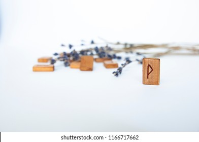 Thurisaz. Scandinavian runes. Wooden runes on a table on a white background.