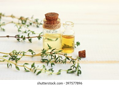 Thyme essential oil. In bottles, with fresh thyme herb twigs.