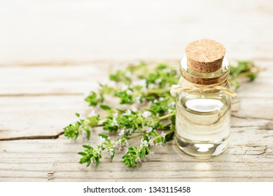 thyme essential oil and thyme flowers on the wooden board