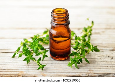 Thyme essential oil and fresh thyme on the wooden table