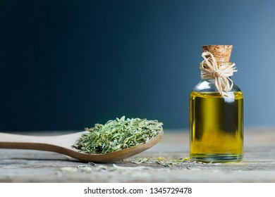 thyme essential oil and Heap of dry thyme in wooden spoon or shovel on wooden background. Dried spice zahter thyme and oil concept