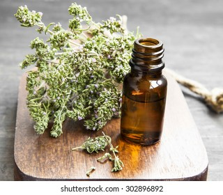 Thyme Herb Essential Oil Bottle on a Wooden Board
