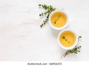 Thyme herbal tea, view from high angle on two cups with tea, space for a text