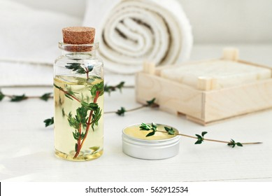 Thyme oil skincare. Bottle of herbal extract, aromatic fresh green twigs, facial cream sample jar, soft focus