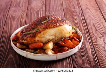 Thyme rooster crown with potatoes and carrots on plate