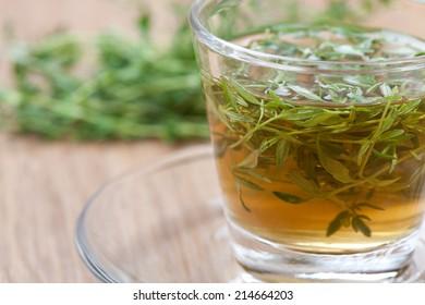 thyme tea with fresh thyme inside teacup on a wooden floor, closeup,
