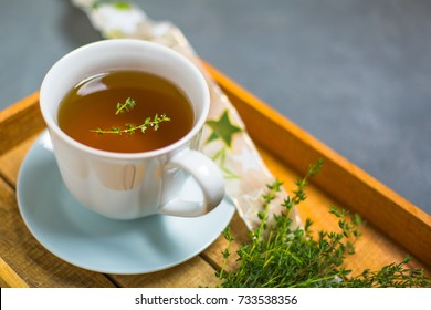 Thyme tea in white cup on a wooden tray side view.